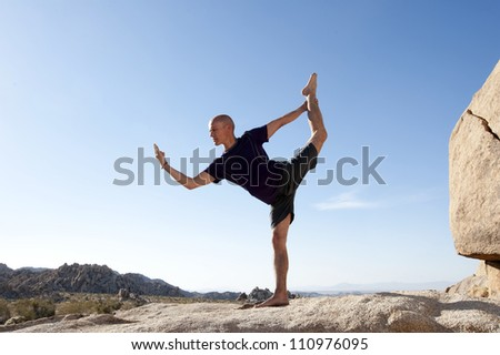 Man in the yoga pose Natarajasana outdoors balanced on a stone surface in the desert.