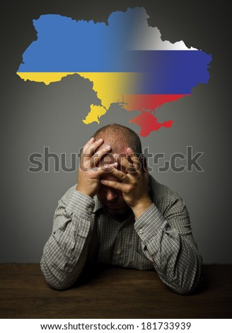 Man in thoughts about the future of Ukraine. Russian and Ukrainian flag. - stock photo