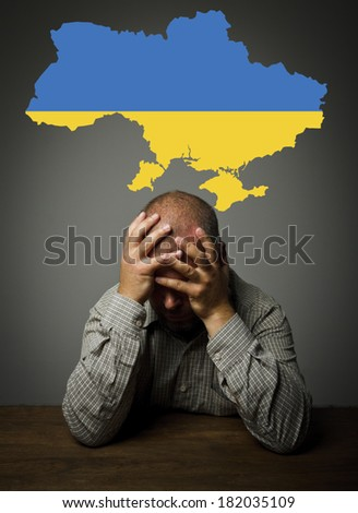 Man in thoughts about the future of Ukraine. Ukraine flag. - stock photo