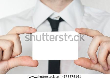Man in tie showing and holding a card - stock photo
