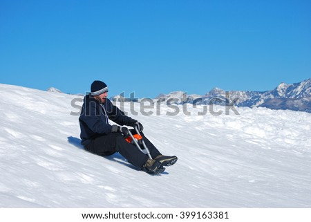 Man in toboggan on a motorcyle sled on a snowhill going down laughing. - stock photo