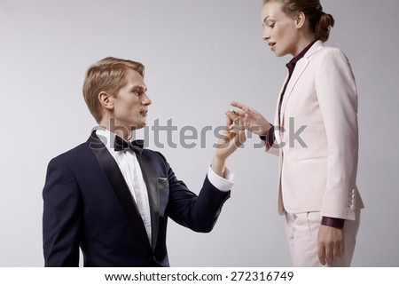 Man in toxedo, and woman in business suit in romantic relation - stock photo