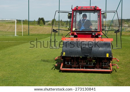 Man in tractor aerating a soccer field - stock photo