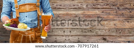 Man in traditional clothes with beer glass and Bavarian specialty. Oktoberfest background