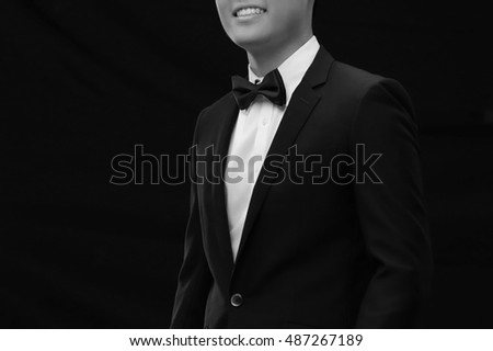 man in tuxedo and bow tie posing. Black and white