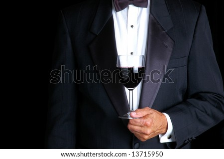 Man in Tuxedo Holding a Glass of Red Wine