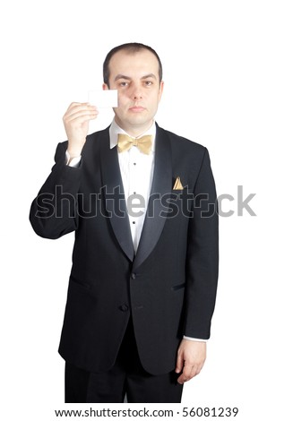 Man in tuxedo holding up blank business card in front of his face - stock photo
