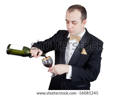 Man in tuxedo pouring red wine in the glass