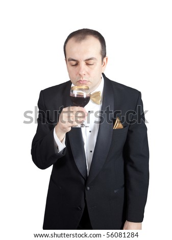 Man in tuxedo smelling wine in the glass - stock photo