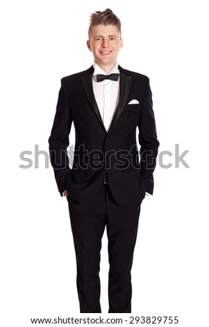 Man in tuxedo standing with hands in pockets. Young elegant smiling man in suite isolated on white