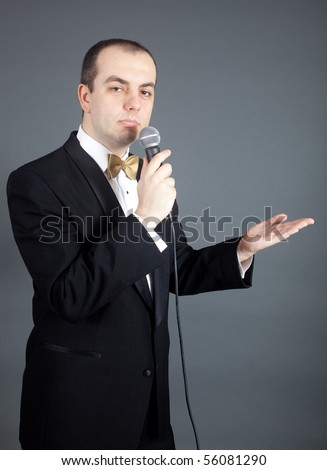 Man in tuxedo talks into microphone - stock photo