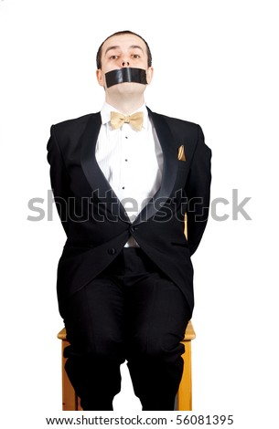 Man in tuxedo tied to a chair and gagged with duct tape