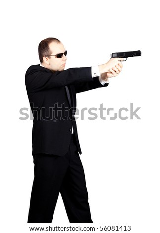 Man in tuxedo with glasses aiming with a gun to the left - stock photo