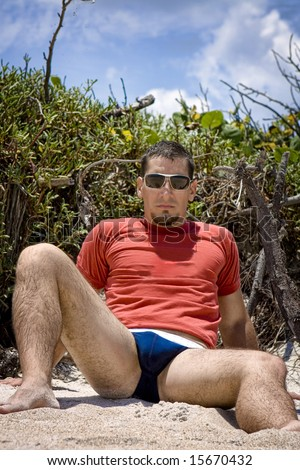 Man in underwear and t-shirt sitting at the beach - stock photo