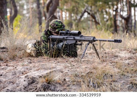 Man in uniform lay on the sand and takes aim at target/British sniper on ground in forest