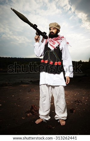 Man in vest with explosives holding RPG rocket launcher - stock photo