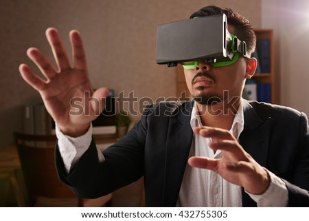 Man in VR headset exploring virtual world - stock photo