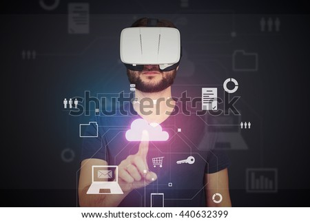 Man in VR-headset is pressing a Cloud icon on imaginary interactive monitor over dark background - stock photo