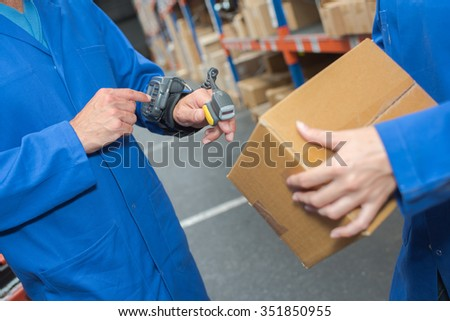 Man in warehouse using hand held scanner - stock photo