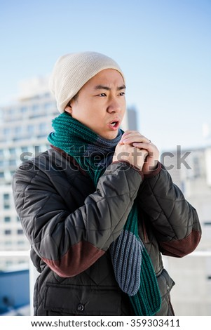 Man in warm clothing blowing his hands against the sky