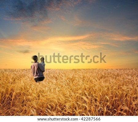 man in wheat field with boy - stock photo