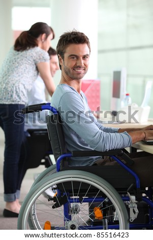 Man in wheelchair at work - stock photo