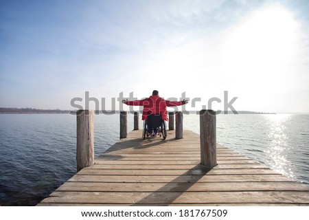 man in wheelchair enjoying his freedom at lake - stock photo
