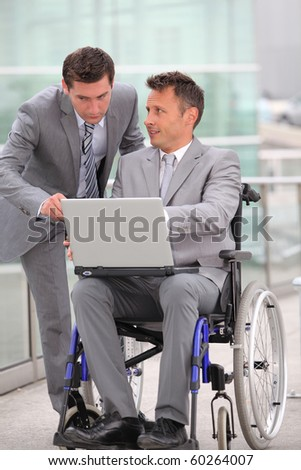 Man in wheelchair in business travel - stock photo