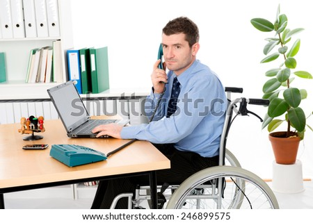 man in wheelchair is working in the office - stock photo