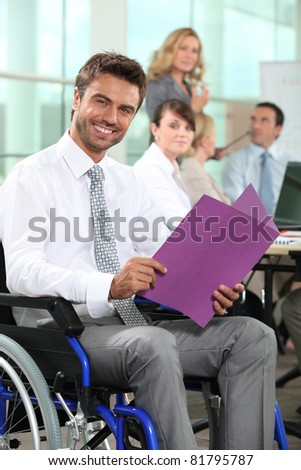 Man in wheelchair looking at notes - stock photo