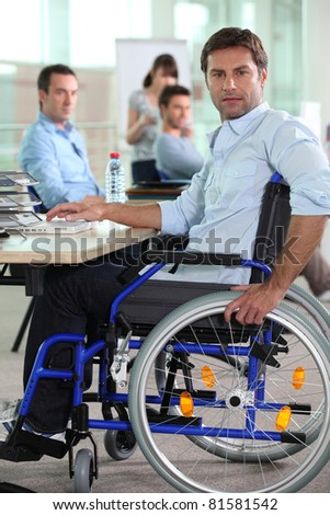 Man in wheelchair on laptop - stock photo