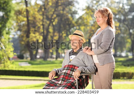 Man in wheelchair sitting with his wife in park on a sunny day - stock photo
