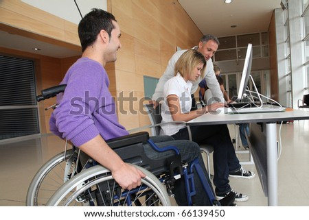 Man in wheelchair working in the office - stock photo