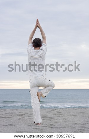Man in white cloths doing yoga on a beach - stock photo