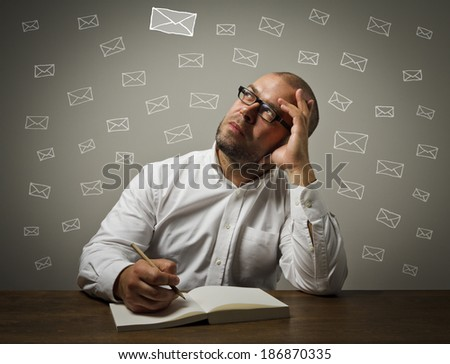 Man in white is sitting at the table and is ready to write something. Man in white looking at the letters. - stock photo