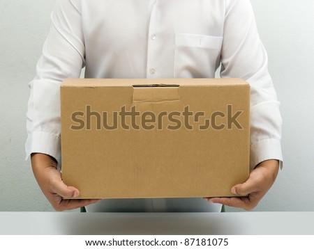 Man in white shirt carry brown paper box hand under - stock photo