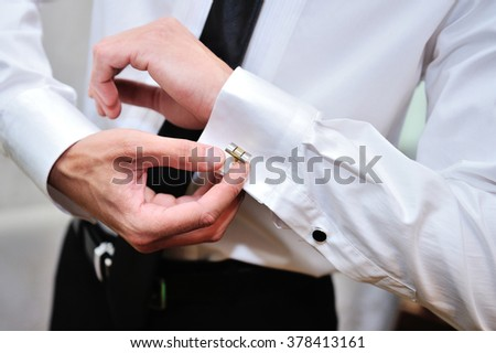 man in white shirt near window dress cufflinks. - stock photo