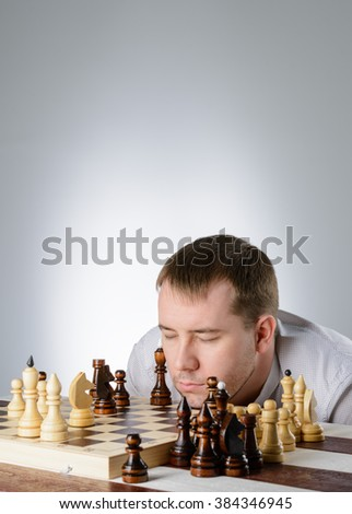 Man in white shirt thinking of the game of chess - stock photo