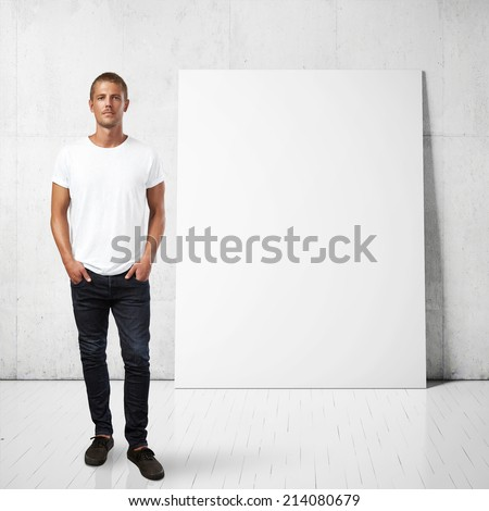 Man in white t-shirt and blank poster on a wall - stock photo