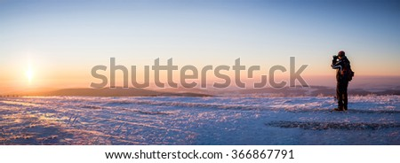 Man in winter clothes and covered his face, standing at the right of panoramic picture of landscape with hills bathed in the glow of sunset. Focus on the man's figure,background slightly out of focus. - stock photo