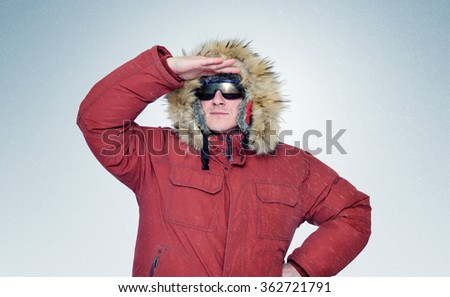 Man in winter clothes and sunglasses, put his hand to his forehead and looks forward  - stock photo