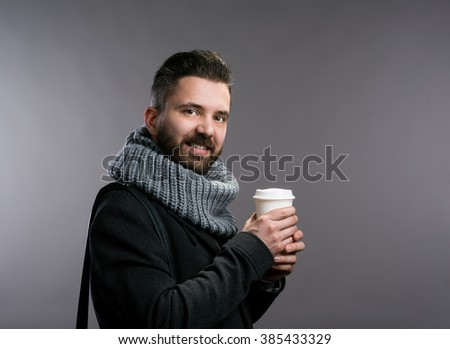 Man in winter clothes holding coffee cup. Studio shot