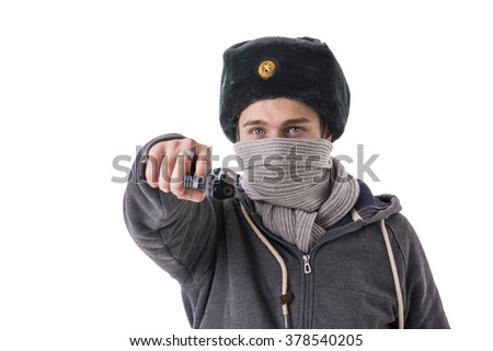 Man in winter hat and scarf threatening with gun.Studio shot.