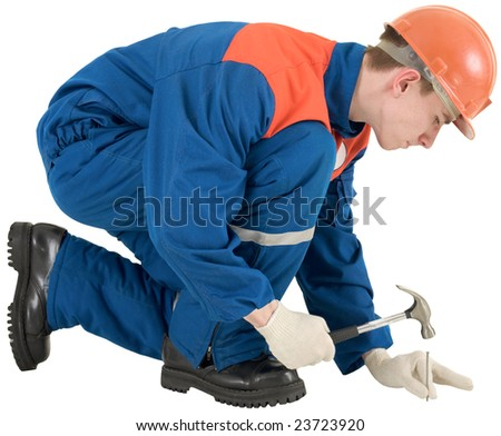 Man in worker overalls with hammer and nail - stock photo