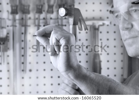Man in workshop with hammer and nail