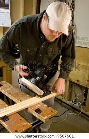Man in workshop with skillsaw cutting a piece of wood - stock photo