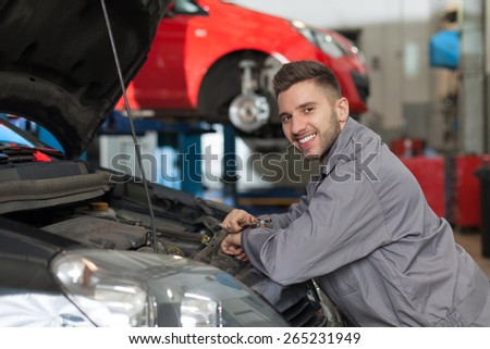 Man in workwear posing with a wrench in an auto repair shop.