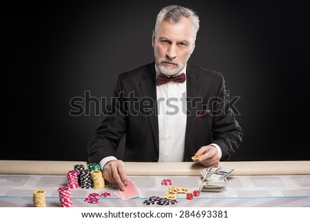 Man in years sitting at poker table, playing poker and looking seriously at camera. The chips and money are on table - stock photo