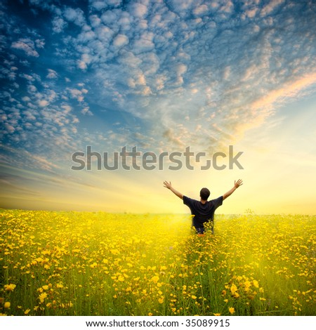 man in yellow flower  field under beautiful sky - stock photo