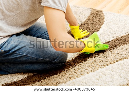 Man in yellow gloves cleaning carpet - stock photo
